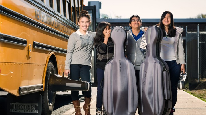 Middle School children standing by a school bus with musical instruments